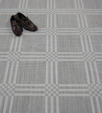 Bellbridge Boxwood Garden Wall Gray 5208/910 shown with pair of shoes used as props. Boxwood is a textured loop pile wilton fabricated with striated yarns that create a box design.
