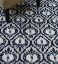 Bellbridge Cezanne Navy 7/5250 stylized with chair. Cezanne is a flatweave with a modern damask design. This colorway has tones of navy, beige and white.