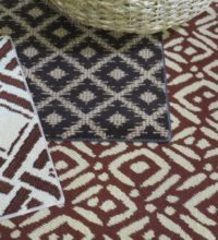 Bellbridge New Kraal Collection featuring Ikaya 68086, Inkosi 68076 and Sangoma 68066. The designs in this collection are of axminster construction (cut pile) featuring various ethnic designs. Image also shows wicker basket used as prop.