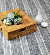 Bellbridge Linen Stripe color Navy/ Denim 290/5703 stylized image. magazine. Image shows Linen Stripe carpet and props - wicker basket, flowers, and vases. Linen Stripe has stripes that down the length of the carpet. The linear design is created by 3 colors - navy, denim and white.