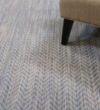Bellbridge Riverbed Shallow Water 41/5730 with chair as prop. Riverbed is a herringbone pattern created with striated yarns of blue, camel and beige. Image shows several pattern repeats of the carpet.