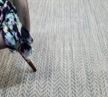 Bellbridge Riverbed Reflection 39/5730 shown with chair and colorful scarf. Riverbed is woven with various striated yarn colors creating the herringbone pattern. The image shows several pattern repeats of Riverbed.