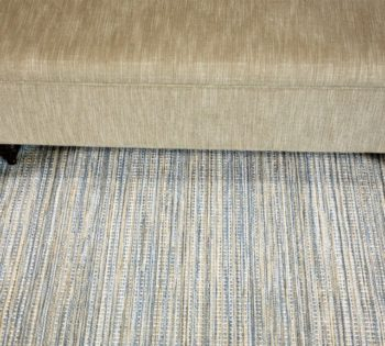 Bellbridge Waterfall Deep Water 41/5732 image with prop - bench and two decorative blue vases. Waterfall Deep Water has variegated blue and camel colored yarns that create a linear pattern down the length of the carpet.