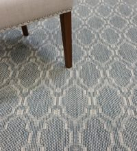 Bellbridge Bridgehampton Blue Shoreline 9640/5217 shown with chair. Bridgehampton is a flatwoven loop pile with has a moroccan design. Colors are dk blue and lt beige.