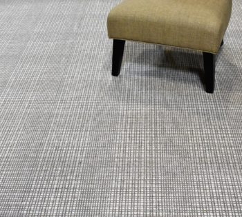 Bellbridge Grand Central Pewter Ivory 530/1501 shown with chair. Grand Central Pewter Ivory is hand loomed with two hearthered yarns (pewter/ivory) creating a large plaid design.