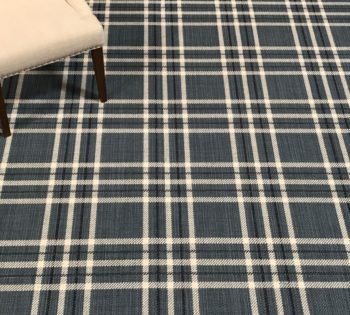 Bellbridge L-Squared Washed Denim color 5710/ 88 . Image shows several repeats of L-Squared and chair used as prop. L-Squared is a woven flatweave fabricated with heathered yarn in background and 2 dominant top colors (navy/white) to create a plaid design.