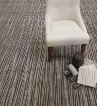 Bellbridge Capella Cosmic Dust 55224/44 stylized with chair and various finishing options for fabricated rugs. Image also shows chain set of Capella featuring all available colors. Capella is a cut/loop pile wilton carpet using two colors designed to create a staggered linear design.