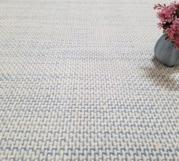 Bellbridge Trace Blue / Lt Blue 1518/406 shown with vase and flowers. Trace has a natural white background with blue yarns tracing along the weave structure.
